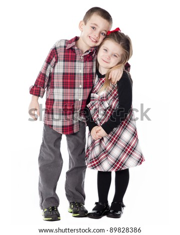 Boy and Girl embracing in dressy clothes in studio isolated on white - stock photo