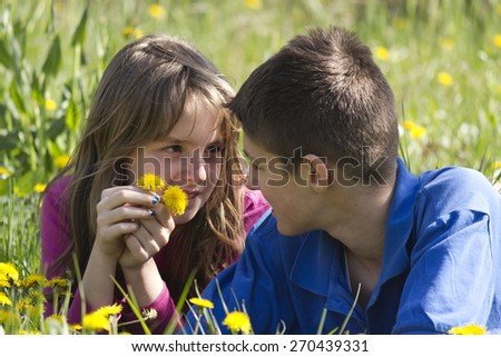 Boy and girl enjoying in the nature .They lie in a field surrounded by dandelion. - stock photo