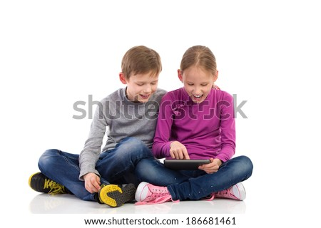 Boy and girl enjoying new tablet. Young girl and boy sitting on the floor with crossed legs and using tablet. Full length studio shot isolated on white. - stock photo