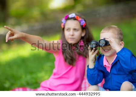 Boy and girl exploring the environment with a binocular - stock photo