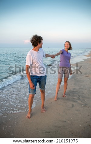 Boy and girl go on the beach during sunset