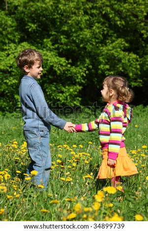 boy and  girl handshaking among blossoming dandelions, focus on boy - stock photo