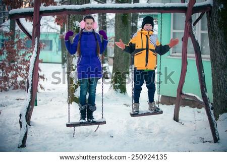 boy and girl having fun in winter park - stock photo