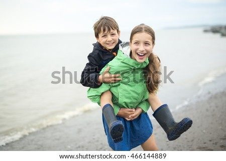 boy and girl having fun on rain close to a sea