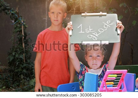 Boy and girl holding chalkboard with words first grade. Outdoor portrait