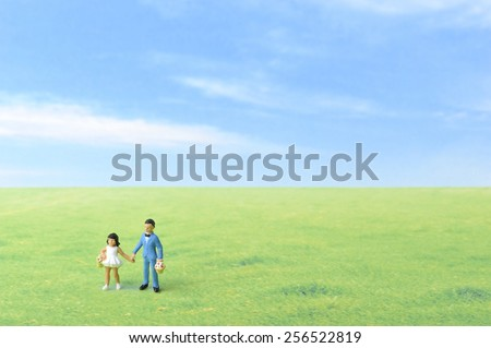 Boy and girl holding hands with blue sky and grassland