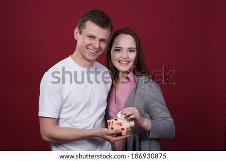 Boy and girl holding piggy bank - stock photo