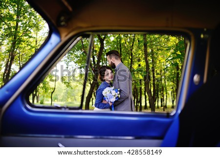 boy and girl hugging near the blue retro car. Boy and girl laughing and hugging in a forest.