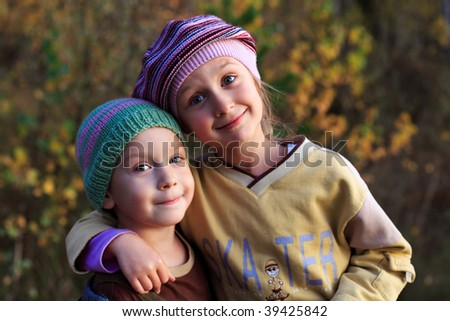 boy and girl in a cap on the nature, autumn - stock photo