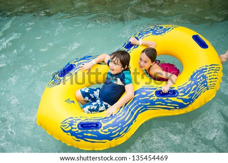 Boy and girl in a tube in a pool at Jay Peak's waterpark - stock photo