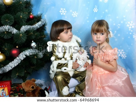 boy and girl in costume around Christmas tree
