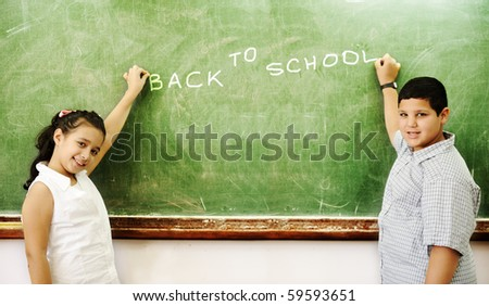 Boy and girl in front of school board writing: BACK TO SCHOOL - stock photo