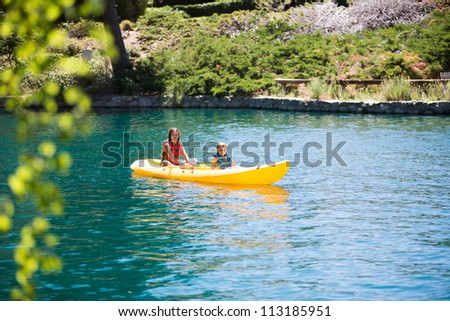 Boy and girl in kayak - stock photo