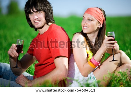 Boy and girl in kerchief with wineglasses - stock photo