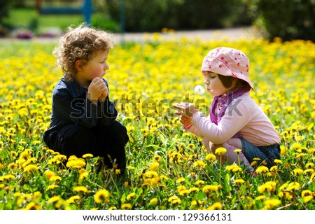 boy and girl in summer flowers field - stock photo
