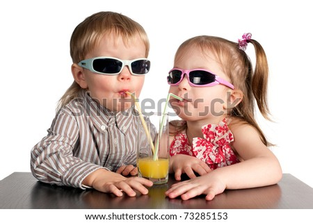 boy and girl in sunglasses drinking juice from glass - stock photo