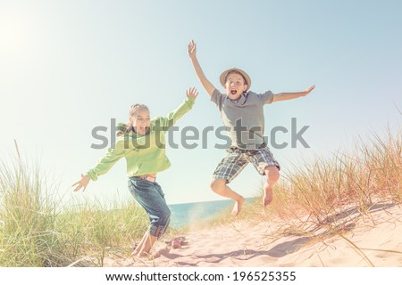Boy and girl jumping in the dunes at the beach - stock photo
