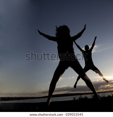 boy and girl jumping up at different levels on the background of the sunset sky with clouds - the symbol of victory success and achieving - stock photo