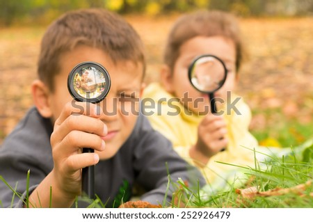 boy and girl look through a magnifying glass on the background of green grass and yellow leaves - stock photo