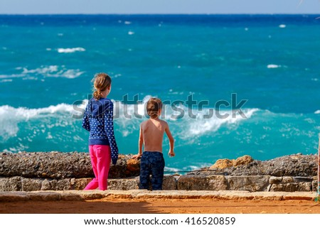 Boy and girl looking at storm waves on the waterfront of Chania on a sunny day. - stock photo