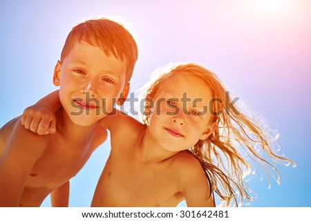 boy and girl looks into the camera on the sunny beach over the blue sky - stock photo
