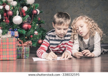 Boy and girl lying on the floor under the Christmas tree. Next to the gifts. They are writing wish list for Santa. Waiting for Christmas. Celebration. New Year. - stock photo