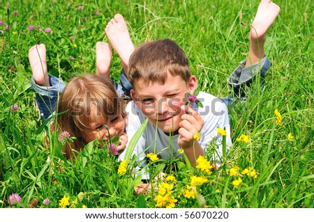 Boy and girl on a green meadow - stock photo
