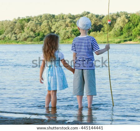 boy and girl on a summer day in the river.toned - stock photo