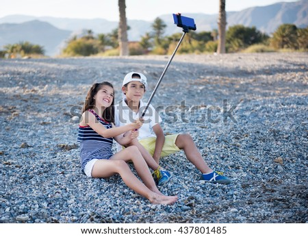 Boy and girl on the beach doing selfie