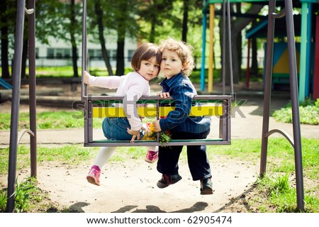 boy and girl on the swings - stock photo