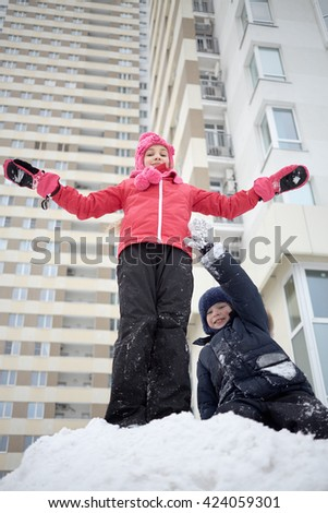 Boy and girl play on snow pile at courtyard near residential hous. - stock photo