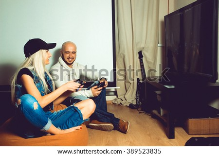 boy and girl playing computer games on the TV. concept of leisure entertainment and fun - stock photo
