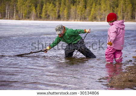 Boy and girl playing in the lake - stock photo