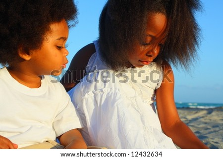 Boy and girl playing in the sand - stock photo
