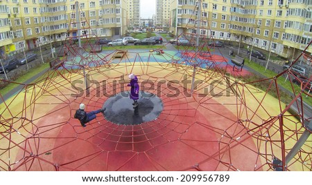 Boy and girl playing on the playground in courtyard, aerial view - stock photo
