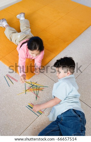 Boy and girl playing pick up sticks - stock photo
