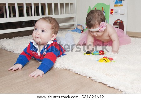 boy and girl playing together on the carpet at home or in the kindergarten