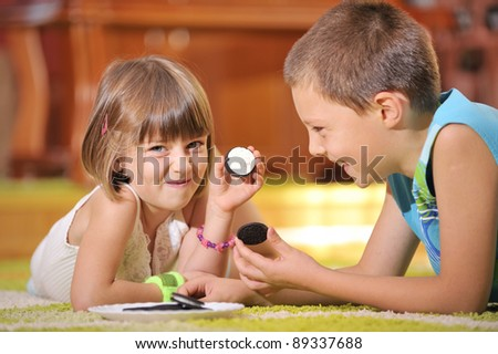 boy  and girl playing with cookies - stock photo