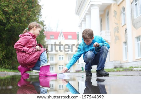 Boy and girl playing with paper boats in puddle on a cloudy day - stock photo