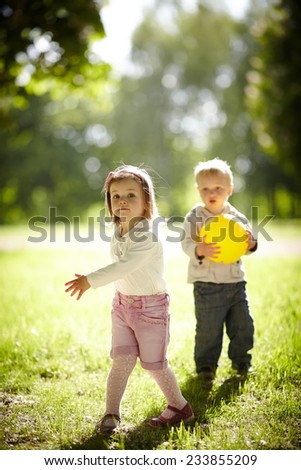 boy and girl playing with yellow ball - stock photo