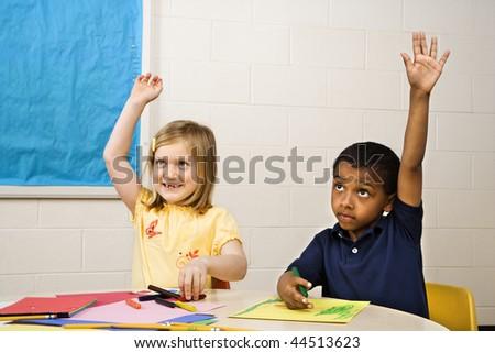 Boy and Girl raising hands in art class. Horizontally framed shot. - stock photo