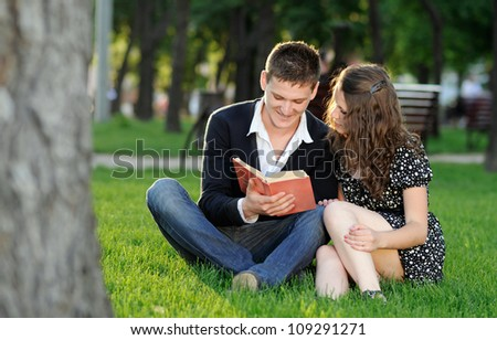 Boy and girl reading a book sitting on the grass in the park