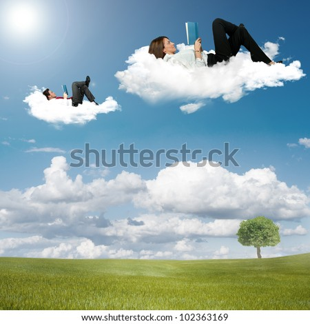 Boy and girl reading book on the clouds - stock photo
