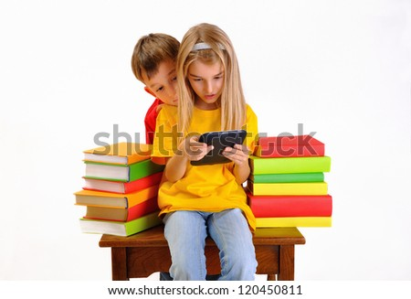 Boy and girl reading e-book surrounded by several books, isolated on white background - stock photo