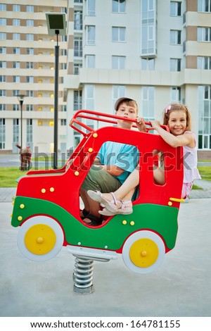 Boy and girl ride on spring swing at children playground in house yard - stock photo