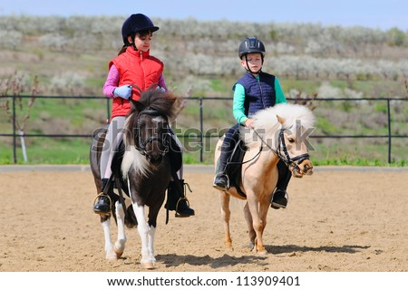 Boy and girl riding a pony - stock photo