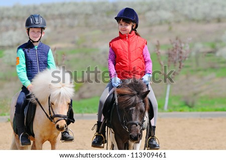 Boy and girl riding a pony