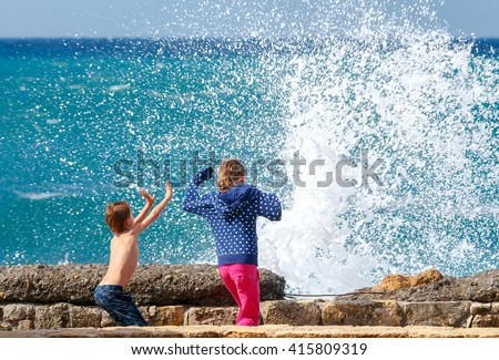 Boy and girl running away from the waves on the waterfront of Chania. - stock photo