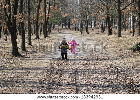 Boy and girl running on a spring forest - stock photo