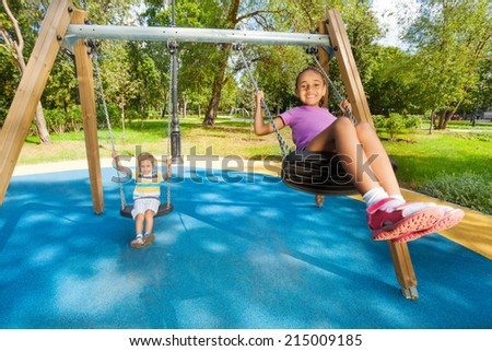 Boy and girl singing on swings - stock photo